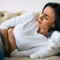 Dysmenorrhea. Close-up photo of a woman, who is lying on her sofa and holding her stomach with suffering facial expression.