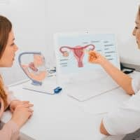 gynecologist communicates with her patient, pointing to the structure of the uterus, on her comput er.